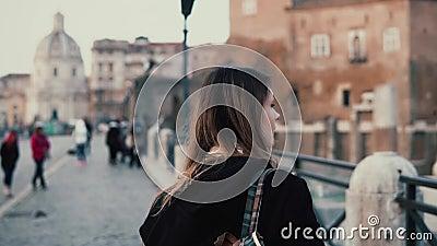 Jovem mulher que anda no centro de cidade, Roman Forum O viajante fêmea toma a foto de ruínas velhas da cidade Menina que explora filme