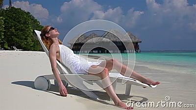 Jovem mulher que aprecia férias em um vadio do sol na praia tropical Movimento lento vídeos de arquivo