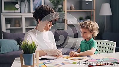 Jovem mulher que ensina seu filho pequeno fazer em casa a colagem de papel na tabela vídeos de arquivo
