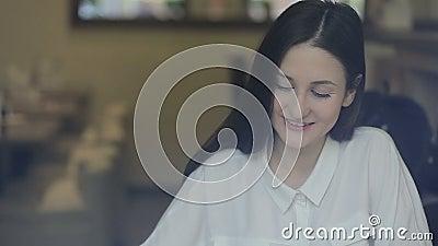 Jovem mulher que fala no telefone celular no café video estoque