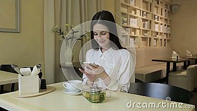 Jovem mulher que fala no telefone celular no café vídeos de arquivo