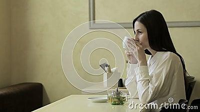Jovem mulher que fala no telefone celular no café filme