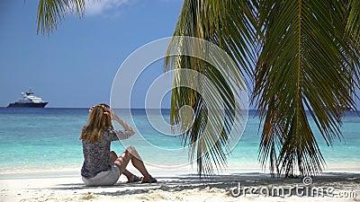 Jovem mulher que senta-se pelo oceano sob uma palma video estoque