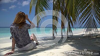 Jovem mulher que senta-se pelo oceano sob uma palma filme