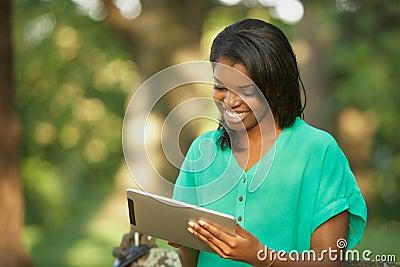 Jovem mulher que usa o computador da tabuleta