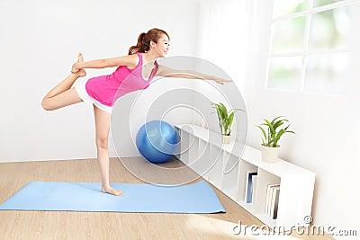 Jovem mulher saudável que faz a ioga em casa