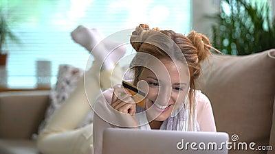 A jovem mulher usa um encontro em linha dourado do cartão de crédito no sofá Tiro da zorra filme