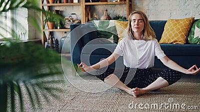 A jovem senhora flexível está relaxando na pose praticando da ioga da borboleta da posição de Badha Konasana em casa que aprecia  filme