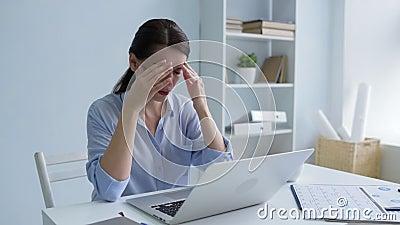 Jovem senhora pobre que esforça-se com a dor de cabeça no trabalho vídeos de arquivo