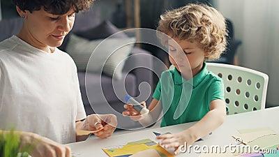 Jovem senhora que ensina seu filho fazer colagens usando o papel, a vara da colagem e as tesouras filme