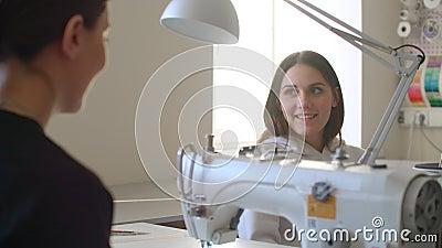 A jovem trabalha com uma máquina de costura e verifica pontos quando seu colega vem até ela com um esboço Mulheres filme