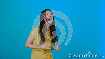 Joven asiática con overoles sobre un aislado muro azul con una expresión facial escandalizada 4K almacen de metraje de vídeo