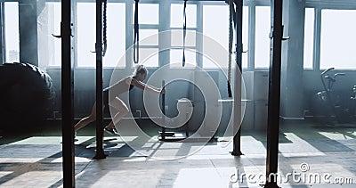 Joven atleta caucásica con vista lateral haciendo ejercicio con entrenamiento pesado en un gran gimnasio atmosférico a cámara l almacen de metraje de vídeo