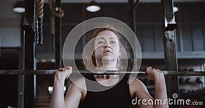 Joven atleta de cabello rojo muy guapa levantando un pesado travesaño, ejercicio extremo en un gran gimnasio profesional almacen de video