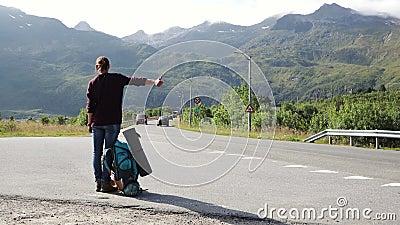 Joven autoestrenadora de pie en la carretera con vistas a las montañas almacen de metraje de vídeo