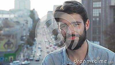 Joven barbudo sonriendo a la cámara con la ciudad en segundo plano almacen de video