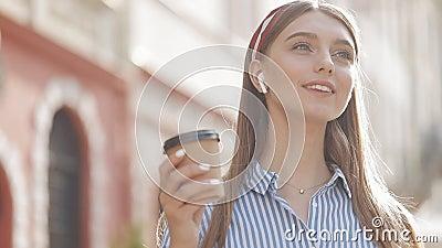 Joven caucásica encantada con el pelo marrón y la cabeza con la camiseta a rayas en los auriculares Sonriente bebida almacen de metraje de vídeo