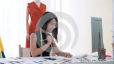 Joven diseñador de moda pensando y esbozando la nueva colección en estudio moderno metrajes