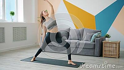 Joven educada haciendo deportes en casa practicando en alfombras de yoga centradas en la actividad almacen de video