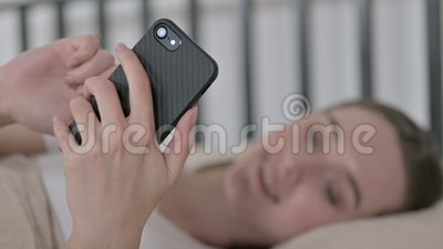 Joven en blur usando smartphone en cama metrajes