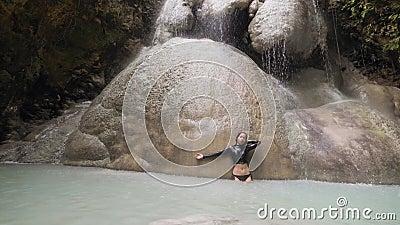Joven en el paraíso tropical bañándose bajo la cascada disfrutando del agua dulce metrajes