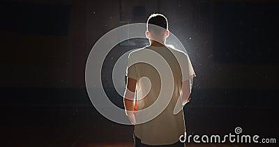 Joven jugador caucásico de baloncesto preparándose para ir detrás de escena silueta de oscuridad de luz Confianza almacen de video