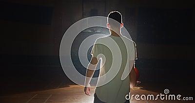 Joven jugador caucásico de baloncesto preparándose para ir tras bastidores, silueta raya de luz. Confidence juega con metrajes