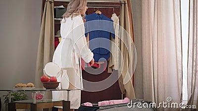 Joven linda chica caucásica abriendo bolso de viaje y poniéndole ropa Feliz joven turista empacando cosas metrajes