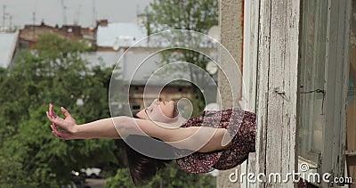 Joven morena yacía sobre la ventana en el umbral de la ventana En el fondo, edificios antiguos y árboles verdes Vídeo de 4K almacen de video