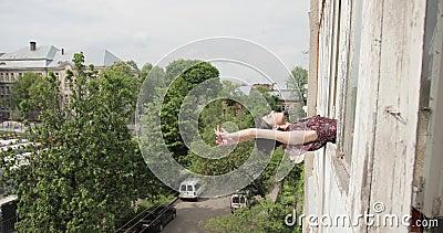 Joven morena yacía sobre la ventana en el umbral de la ventana En el fondo, edificios antiguos y árboles verdes Vídeo de 4K metrajes