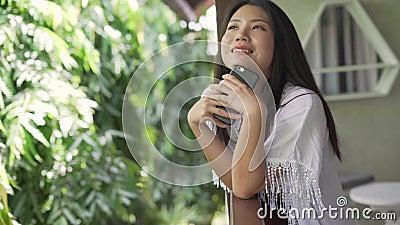 Joven mujer asiática hermosa y feliz por la mañana tomando selfie con teléfono móvil en la terraza o en el balcón de la habitació almacen de metraje de vídeo