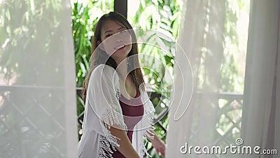 Joven mujer asiática hermosa y feliz que disfruta en la terraza del hotel o en el balcón de su casa sonriendo relajado metrajes