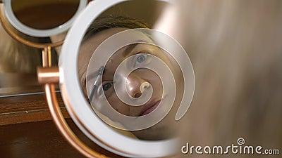 Joven mujer hermosa mirando al espejo y usando cosméticos para pintar cejas almacen de video