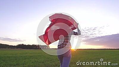 Joven mujer positiva corre por el campo al atardecer con la bandera de China cámara lenta almacen de video