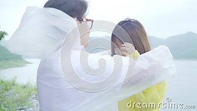 Joven pareja asiática dulce que se siente feliz usando el tiempo romántico jugando a la lluvia mientras usa impermeable parado c almacen de video