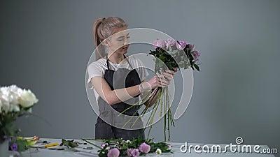 Joven profesional florista usando ramo de delantal de rosas frescas almacen de video