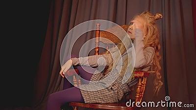 Joven sentada en una silla de madera en una sesión de fotos de moda Niña modelo posando en una silla en un estudio de fotos almacen de video