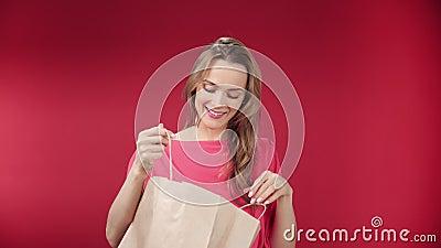 Joven sonriente sorprendida abriendo bolso de compra de papel con emoción positiva almacen de metraje de vídeo