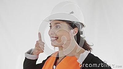 Joven supervisora de cabello oscuro satisfecha en equipos de seguridad sonríe ampliamente y da pulgares hacia arriba con ambas ma almacen de metraje de vídeo