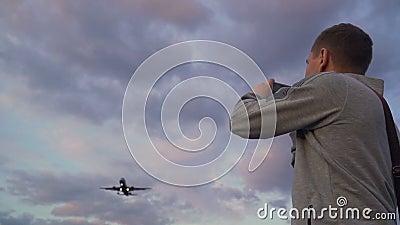 Joven tomando fotos del vuelo de un avión en el cielo de nubes nocturnas. Utilice el smartphone almacen de metraje de vídeo