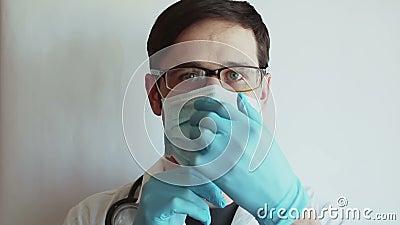 Joven y guapo doctor poniendo mascarillas médicas en preparación para el examen de los pacientes almacen de metraje de vídeo
