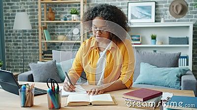 Jovens afro-americanos estudando em casa escrevendo livros de leitura em mesa filme