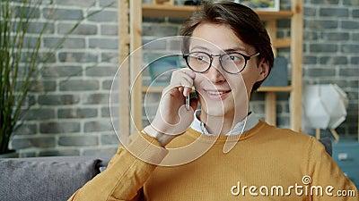 Jovens brunet conversando no telefone celular em um apartamento desfrutando da conversa vídeos de arquivo