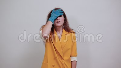Jovens cansadas com casaco amarelo, luvas azuis mantendo as mãos na cabeça video estoque