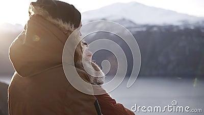 Jovens casais de casacos de inverno abraçando-se, pessoas abraçando-se olhando para a impressionante vista no lago e picos das mo filme