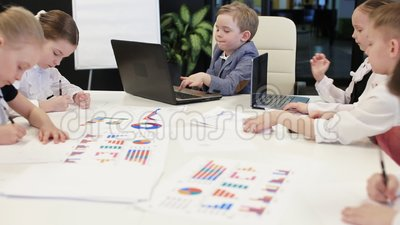 Jovens crianças que sentam-se em portáteis no escritório vídeos de arquivo