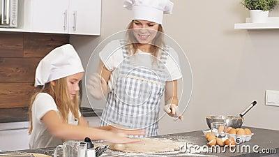 Jovens familiares de cozinheiros envolvidos na preparação de bolo festivo, repelem a massa em conjunto vídeos de arquivo