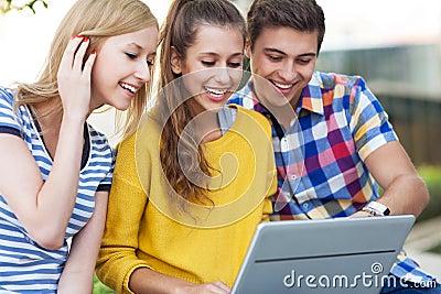 Jovens que olham o portátil junto