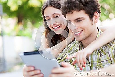 Jovens que olham a tabuleta digital