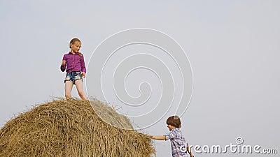 Jovens sem carreira jogando no palheiro no campo da aldeia Garota feliz dançando no palheiro superior na colheita filme